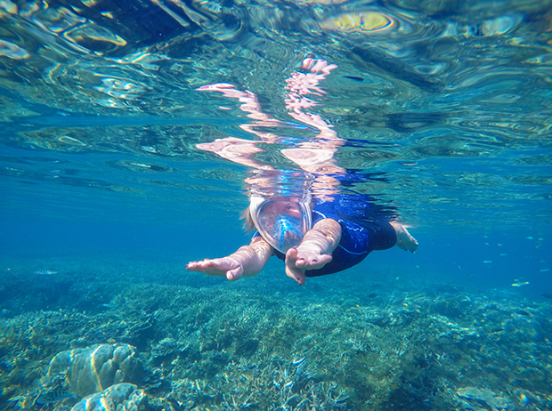 Woman swimming underwater in swimming costume and full-face mask